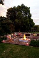 Feuerstelle mit Feuer, gemauerte Sitzbank und Beistelltisch im ...