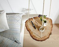 rustikale baumscheibe an seilen aufgeh ngt als nachttisch bild kaufen living4media. Black Bedroom Furniture Sets. Home Design Ideas