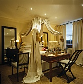 Voluminous drapes surround the iron frame of the four-poster bed in this elegant bedroom