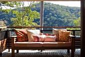 Ein Sofa mit Kissen auf einer Terrasse