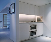 White kitchenette in open-plan living space