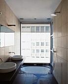 Modern bathroom with floor-level bathtub in front of floor to ceiling window