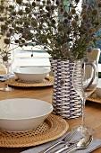 Festlich gedeckter Tisch mit Trockenstrauss in dekorativem blau-weißem Keramikkrug und weisse Suppenteller auf geflochtenen Sets