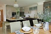 Elegante Küche mit Korbhockern an Küchenblock und festlich gedeckter Tisch mit geflochtenen Platztellern im Vordergrund