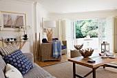 Flechtsessel, Textilien in Blautönen und vielfältig gestaltetes Interieur aus Wurzelholz in offenem maritimem Wohnraum mit Ausblick zum Garten