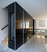 schwarzer hochgl nzender einbauschrank im flur vor treppe auf poliertem betonboden bild kaufen. Black Bedroom Furniture Sets. Home Design Ideas