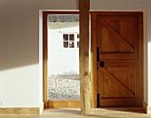 holzst tze vor raumhohem fenster und rustikaler haust r aus holz bild kaufen living4media. Black Bedroom Furniture Sets. Home Design Ideas