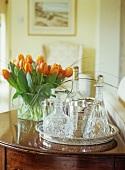 Crystal decanters on silver tray next to bouquet of orange tulips
