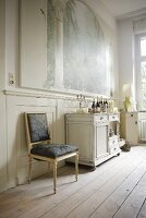 High-ceilinged period room with antique furniture on simple wooden floorboards
