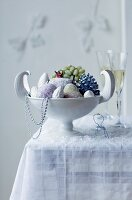 Candied fruit in a white bowl and two glasses of champagne on table