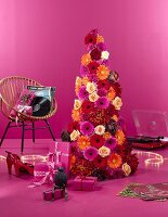 A pink showroom - presents and a cone-shaped Christmas tree decorated with flowers
