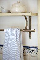 Tea towel over steel bar fixed below shelf