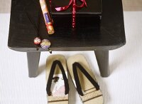 Japanese flip flops under black wooden Japanese table, box, wrapped incense sticks