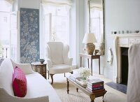 A traditional sitting room with fireplace, upholstered sofa and wing back armchair, French doors, wall hanging