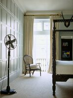 A traditional bedroom with painted panelling, carved wooden four poster bed, cream curtains, armchair, floor fan