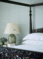 A detail of a traditional bedroom with painted panelling, carved wooden four poster bed, bedside table, lamp