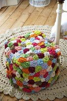 A stool made of colourful crocheted flowers on a crocheted rug