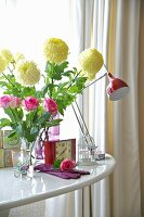 A bunch of flowers in a glass vase and an alarm clock in front of a desk lamp in a white table