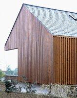 neubauhaus mit teilweiser holzverkleidung und gartenmauer aus ziegeln bild kaufen living4media. Black Bedroom Furniture Sets. Home Design Ideas