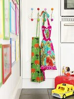 A colourful apron on the wall with toy on the floor in the kitchen