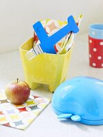 A lunch box, an apple, a child's fork and a napkin