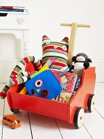 A red handcart full of toys