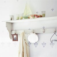 A wooden, shabby chic-style shelf with a row of hooks