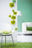 White wall with green flowers and cushion on chair