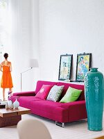 A living room with a high ceiling, a pink sofa and oriental decorative objects