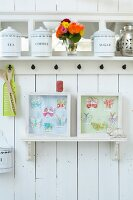 Old storage jars on a white kitchen shelf and framed paper butterflies on a white wooden wall