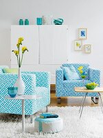 Two turquoise and blue patterned armchairs and side tables in front of white cupboard