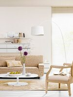 Pale sofa and armchair and white arc lamp in front of window with louver blind
