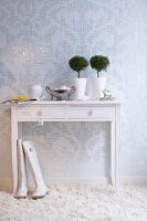 White console table on deep-pile carpet against mosaic wall