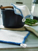 Knitted white pot holders with blue edges