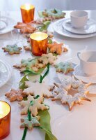 Garland of star-shaped biscuits and ribbon on candlelit table