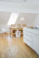 The attic room of an old town house with a kitchen counter and a dining table