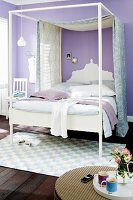 Canopied bed in bedroom with lilac walls