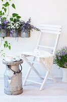 A white wooden chair and a vintage milk churn with flowerpots of campanula and petunias hanging on the wall