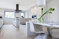 A spacious, modern kitchen in white with a long eating and seating area