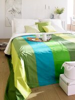 Double bed with striped bedspread in various shades of green