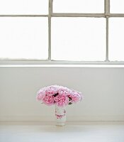 Bouquet of peonies in vase on floor