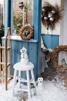 An entrance way decorated with wreaths and a snowman on a stool