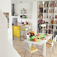An open-plan living room with a bookshelf, a dining table and a kitchen table with stools