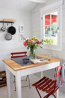 Dining table and red folding chairs in Scandinavian summer house