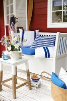 Flowers on a side table and homemade blue and white cushions on a wooden bench on a summery terrace
