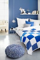 Blue and white bedroom with plexiglass bedside table and pouffe with knitted cover