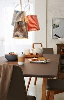 Pendant lamps with knitted shades in brioche stitch hanging above a dining table