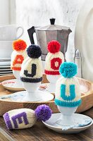 Knitted bobble hat egg warmers with initials