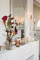 A vase of calla lilies and sprigs of berries, tealights and candle holders on a mantlepiece in front of a mirror