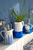 Hand-painted porcelain jugs and bowls in blue-and-white on a wall shelf in a kitchen